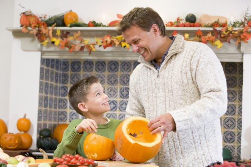 Vater und Sohn, die ein punpkin für Halloween schnitzen lizenzfreie stockfotografie