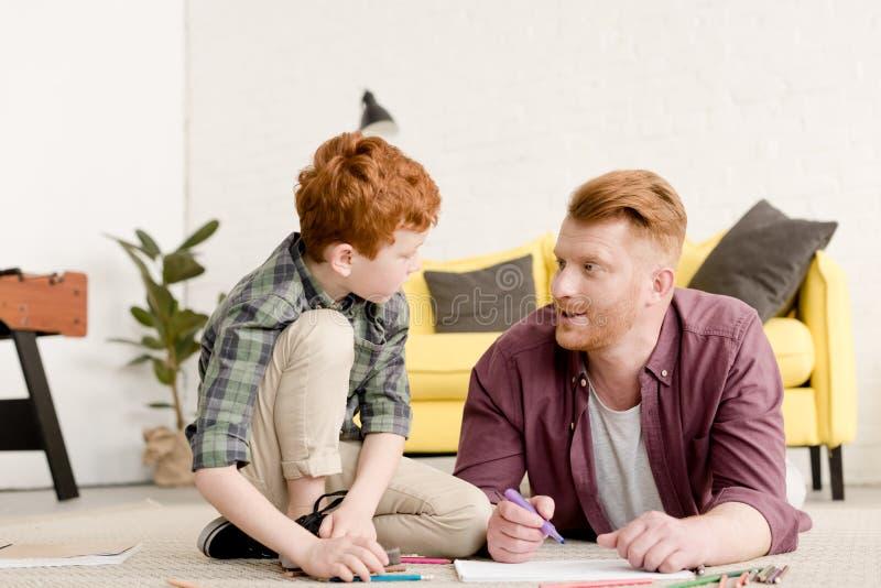 Vater und Sohn, die einander beim zusammen zeichnen betrachten stockfoto