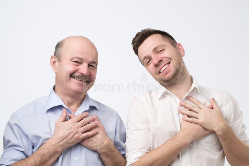 Vater und Sohn, die froh, gefallend mit Kompliment oder Geschenk lächelt lizenzfreie stockfotos