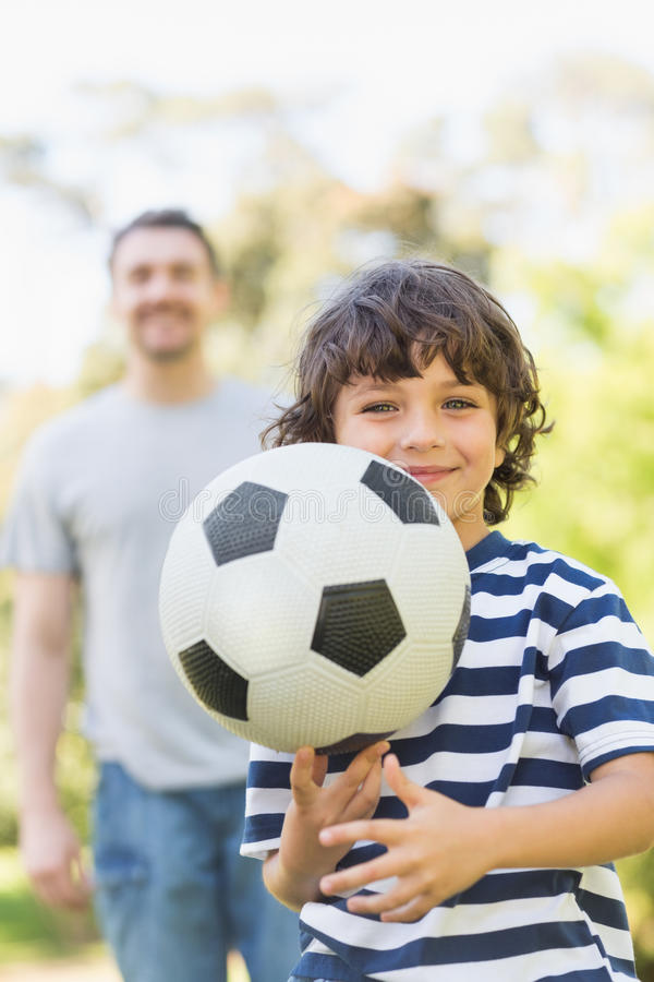 Vater und Sohn, die Fußball im Park spielen stockfotografie