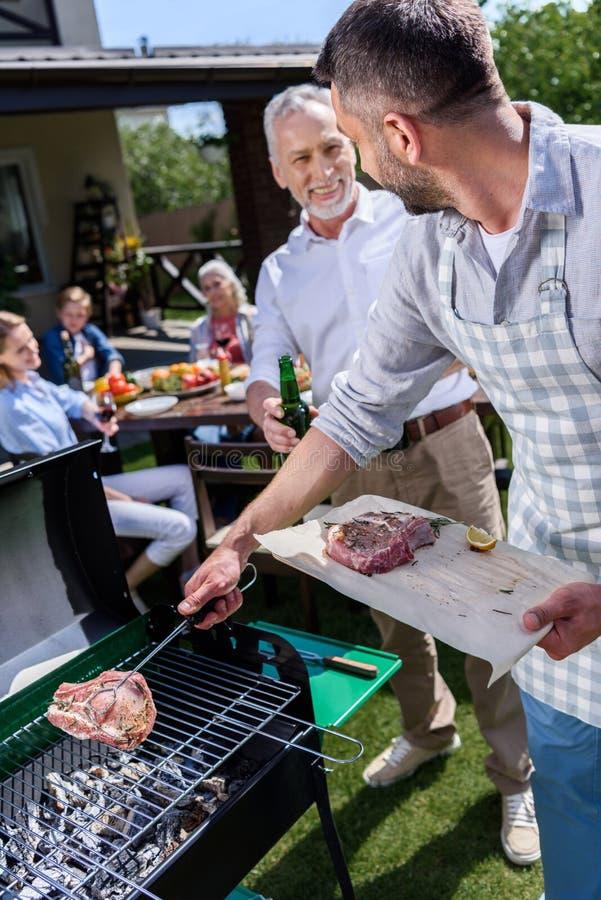Vater und Sohn, die Grill macht und Bier während Familie bei Tisch sitzt draußen trinkt stockbild