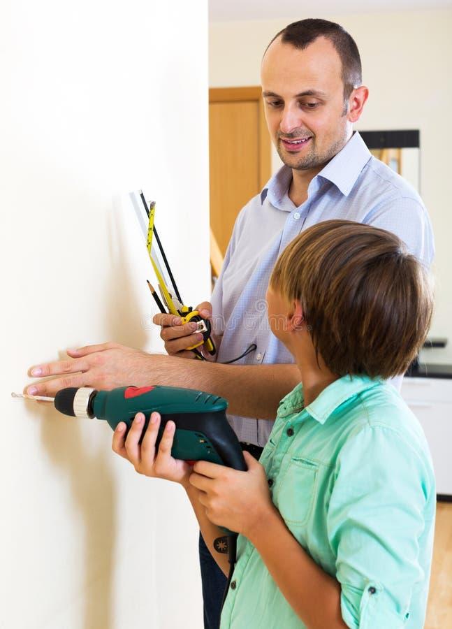 Vater und Sohn, die Haus reparieren lizenzfreies stockbild