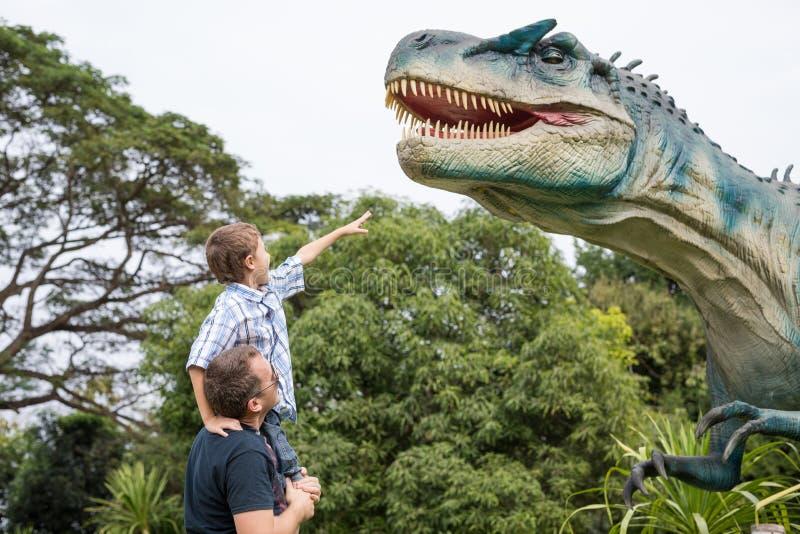 Vater und Sohn, die im Abenteuerdino-Park spielen stockfotos