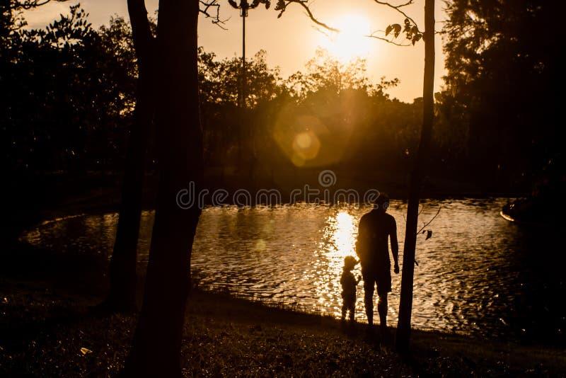 Vater und Sohn, die im Park nahe See zur Sonnenuntergangzeit spielen Konzept der Familienliebe und des Sommerferienschattenbildes lizenzfreie stockfotografie