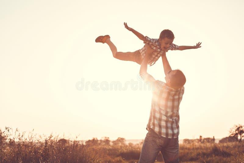 Vater und Sohn, die im Park zur Sonnenuntergangzeit spielen stockfotografie