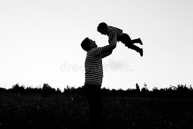 Vater und Sohn, die im Park zur Sonnenuntergangzeit spielen Glückliche Familie, die den Spaß im Freien hat lizenzfreies stockfoto