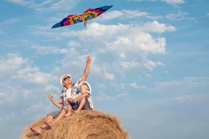 Vater und Sohn, die im Park zur Tageszeit spielen lizenzfreie stockbilder
