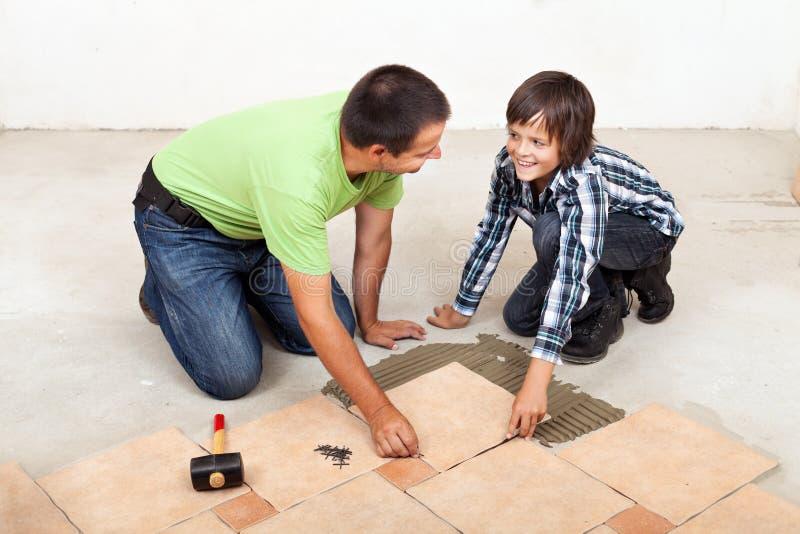 Vater und Sohn, die keramische Bodenfliesen legen stockfotografie