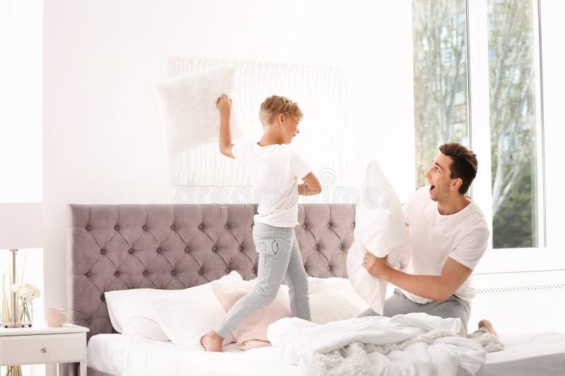 Vater und Sohn, die Kissenschlacht auf Bett haben lizenzfreie stockfotografie