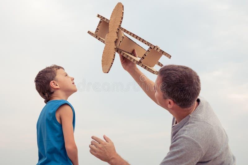 Vater und Sohn, die mit Pappspielzeugflugzeug spielen stockfoto
