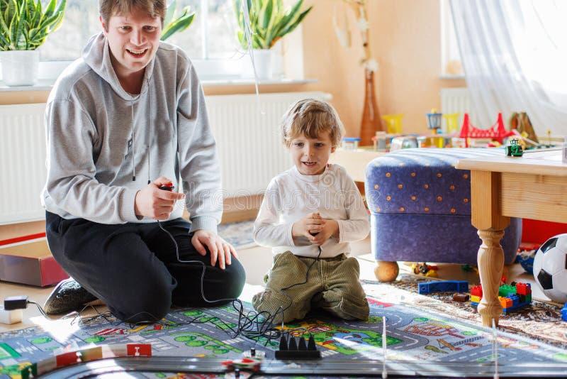 Vater und Sohn, die mit Rennwagen auf Rennbahn zuhause mit Autos spielen lizenzfreies stockbild