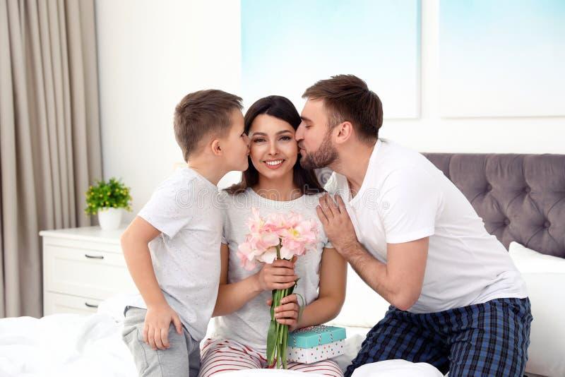 Vater und Sohn, die Mutter im Schlafzimmer begl?ckw?nschen lizenzfreies stockfoto