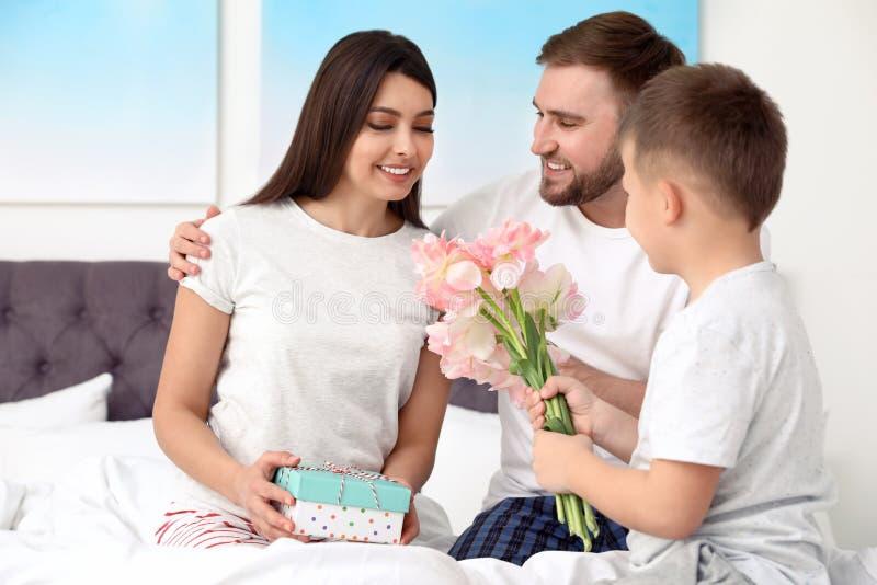 Vater und Sohn, die Mutter im Schlafzimmer begl?ckw?nschen stockbild