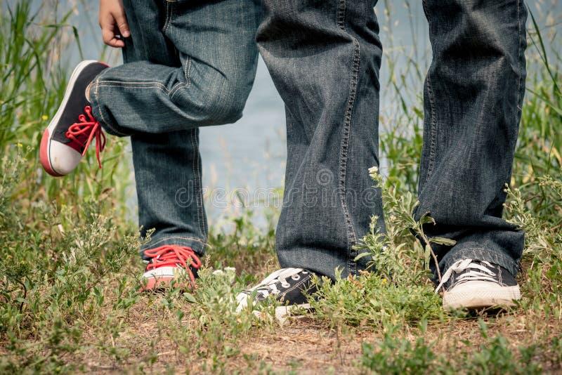 Vater und Sohn, die am Park nahe See zur Tageszeit spielen lizenzfreies stockfoto