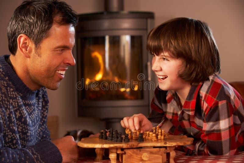 Vater und Sohn, die Schach durch Cosy Protokoll-Feuer spielen lizenzfreie stockbilder