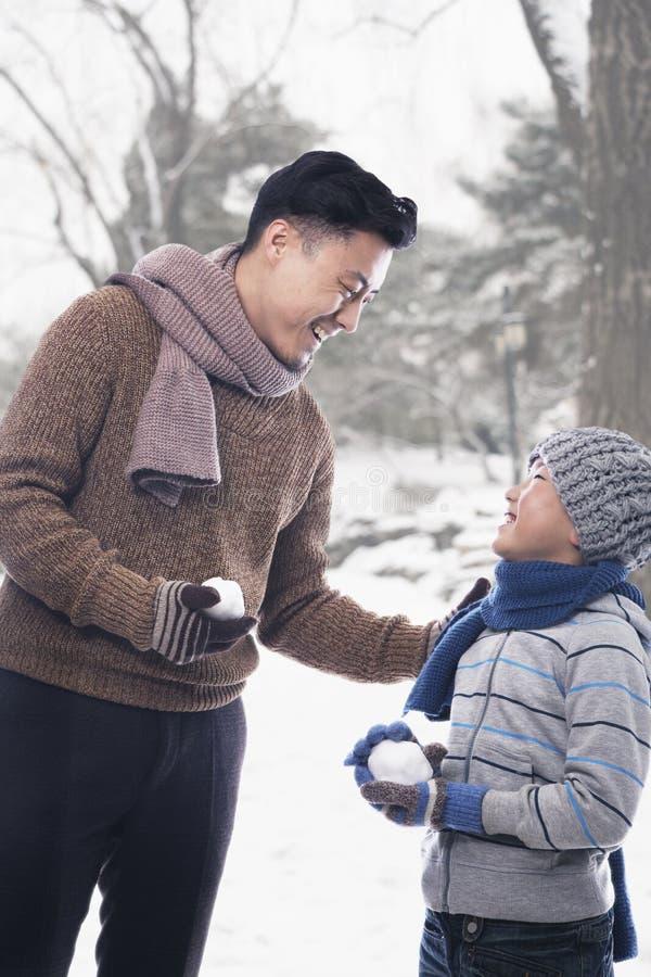 Vater und Sohn, die Schneebälle halten stockfotografie