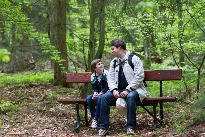 Vater und Sohn, die sich im Wald auf Bank nach einer Wanderung entspannen stockfotos