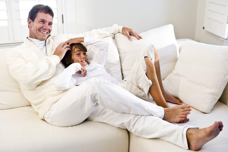 Vater und Sohn, die sich zusammen auf weißem Sofa entspannen lizenzfreies stockfoto