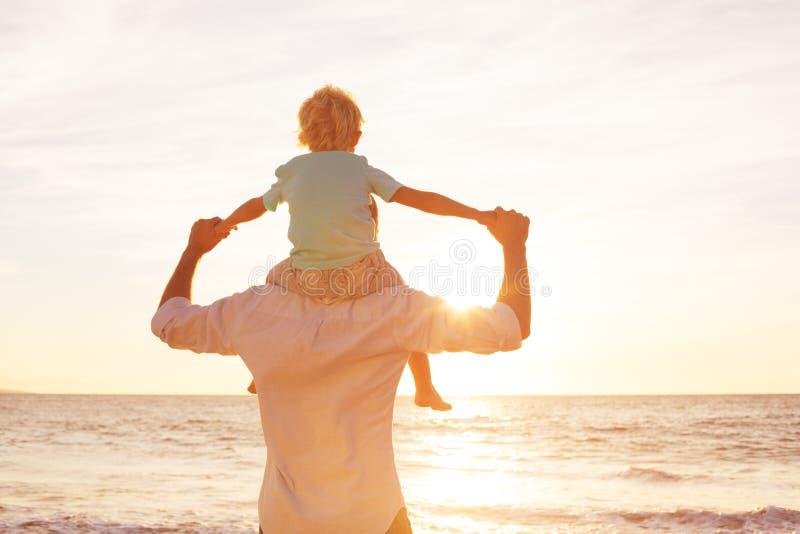 Vater und Sohn, die am Sonnenuntergang spielen lizenzfreie stockbilder