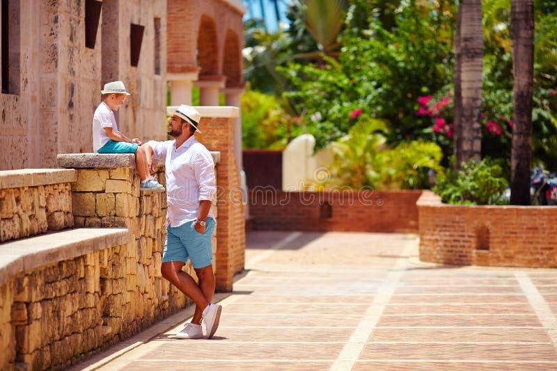 Vater und Sohn, die Spaß auf netter tropischer Straße haben lizenzfreie stockfotos