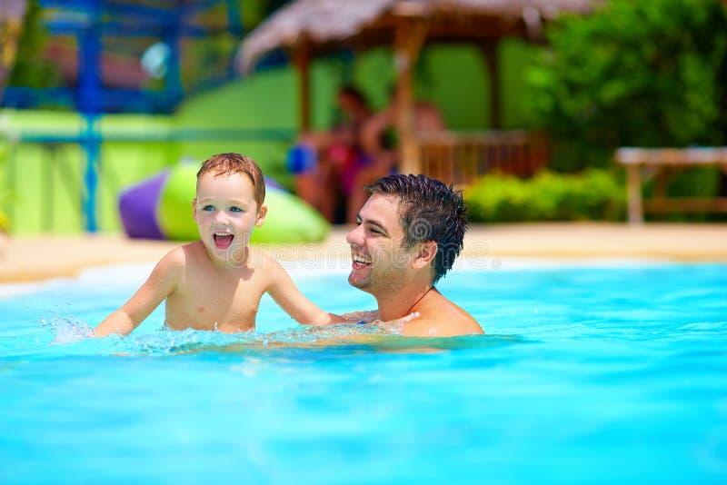 Vater und Sohn, die Spaß im Pool, Sommerferien haben lizenzfreie stockfotos