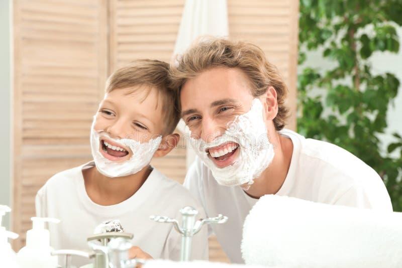 Vater und Sohn, die Spaß mit dem Rasieren des Schaums haben stockfoto