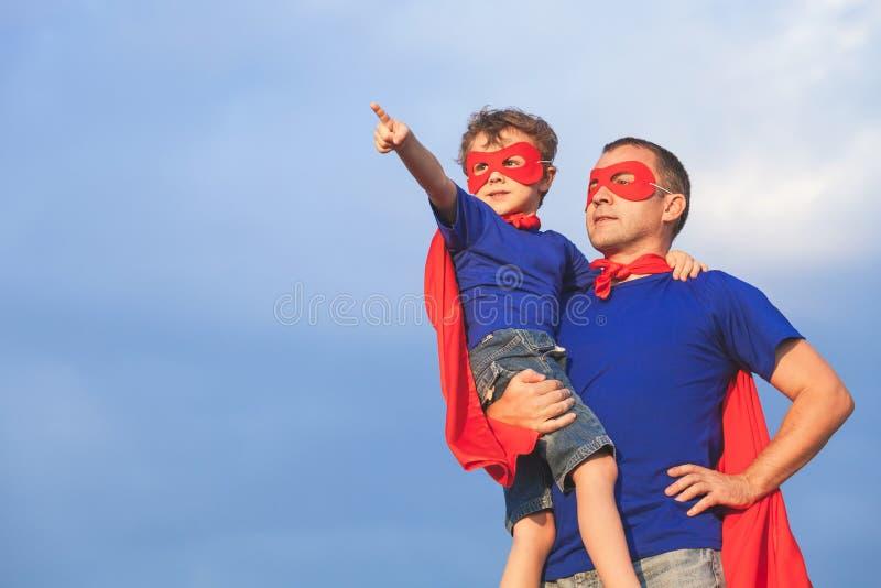 Vater und Sohn, die Superhelden zur Tageszeit spielen stockfoto