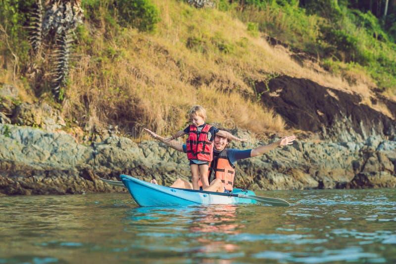 Vater und Sohn, die in tropischem Ozean Kayak fahren stockfoto