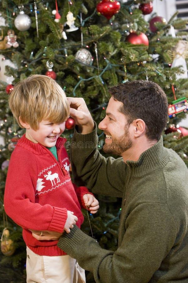 Vater und Sohn, die vor Weihnachtsbaum spielen lizenzfreies stockbild