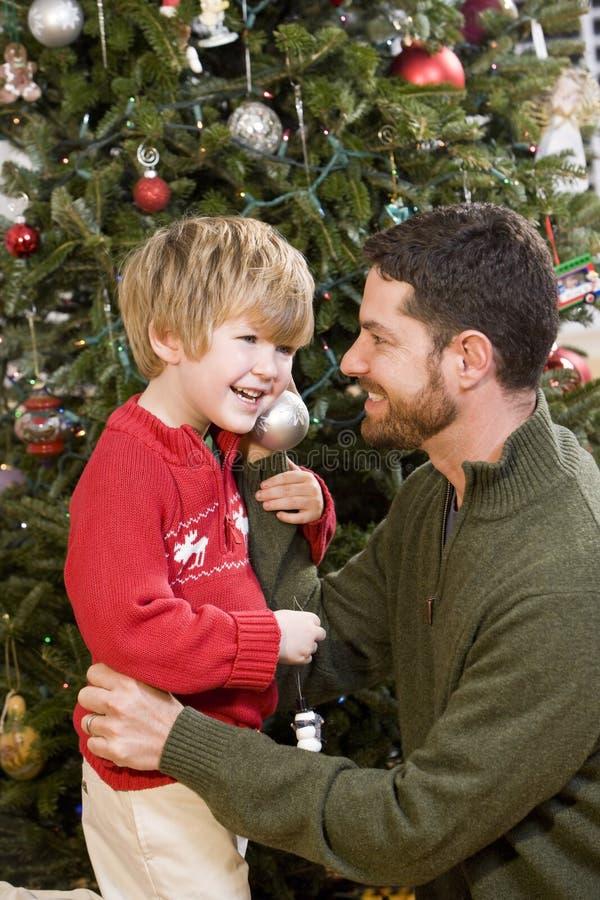 Vater und Sohn, die vor Weihnachtsbaum spielen stockfotografie