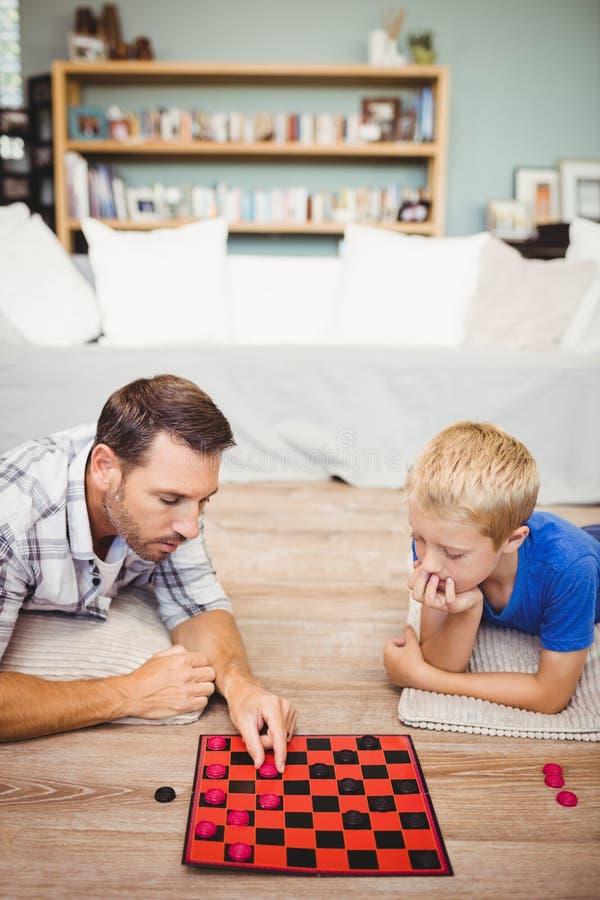 Vater und Sohn, die zu Hause Kontrolleurspiel spielen stockfoto