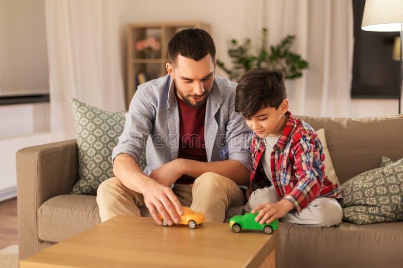 Vater und Sohn, die zu Hause mit Spielzeugautos spielen stockbilder