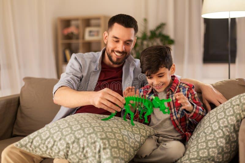 Vater und Sohn, die zu Hause mit Spielzeugdinosaurier spielen lizenzfreie stockfotos