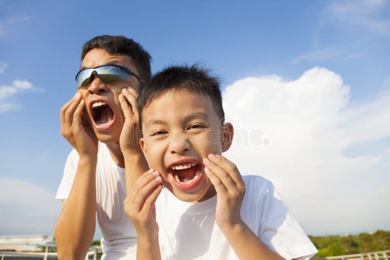 Vater und Sohn, die zusammen eine Grimasse im Park machen stockfotografie