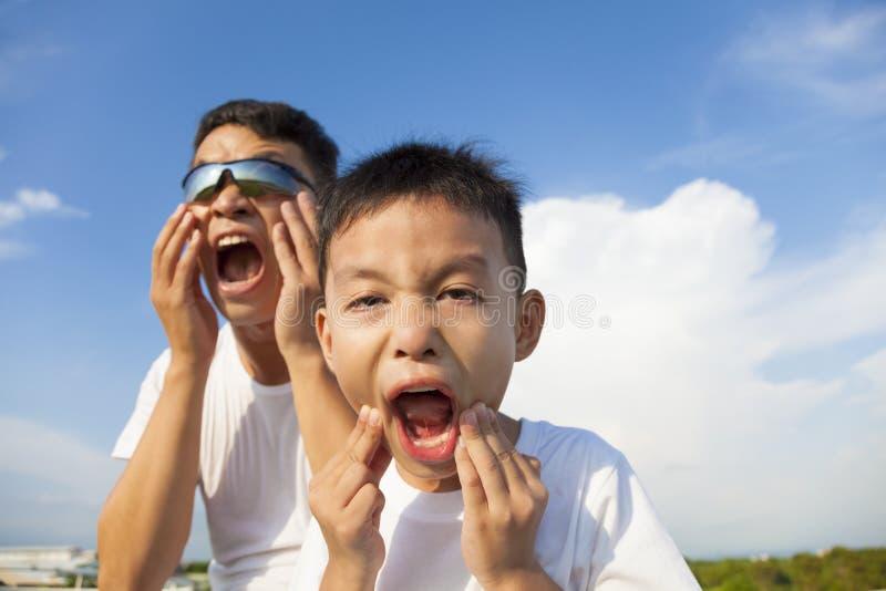 Vater und Sohn, die zusammen eine Grimasse im Park machen stockfoto