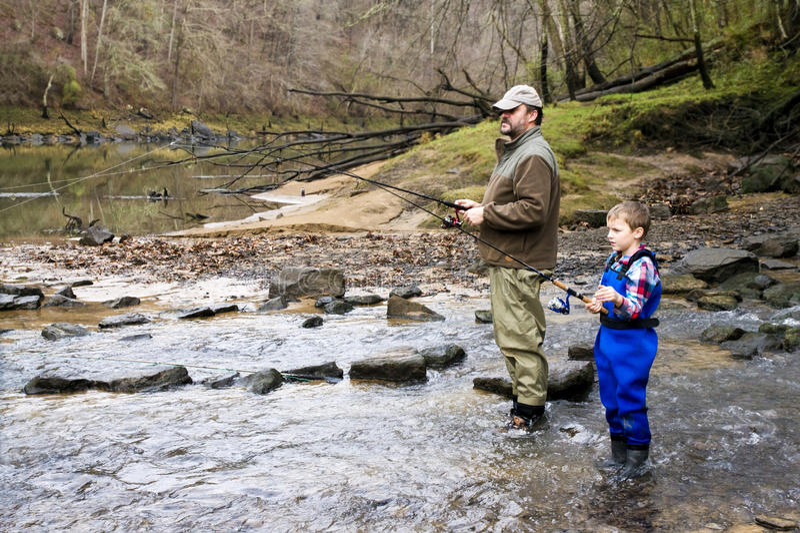 Vater und Sohn, die zusammen Forelle abfangen lizenzfreie stockfotos
