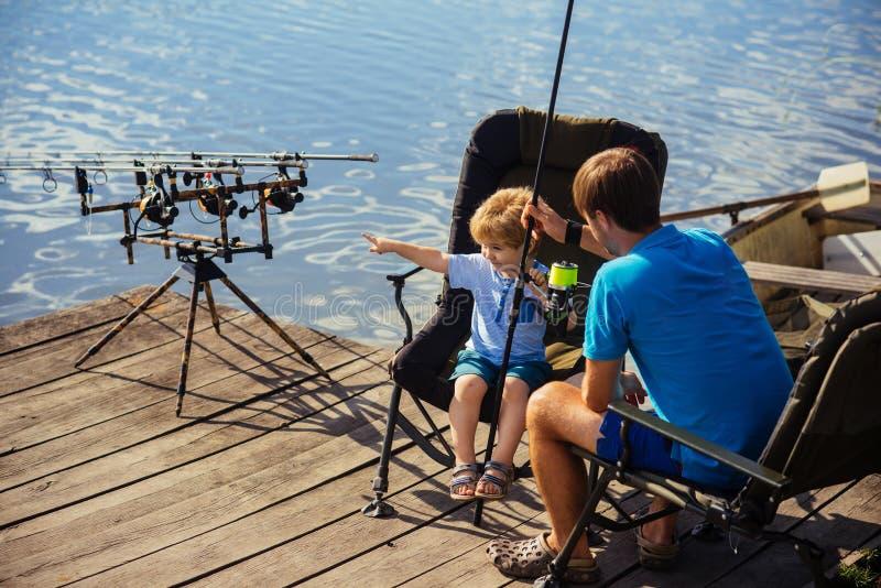 Vater und Sohn, die zusammen im See fischen stockbild