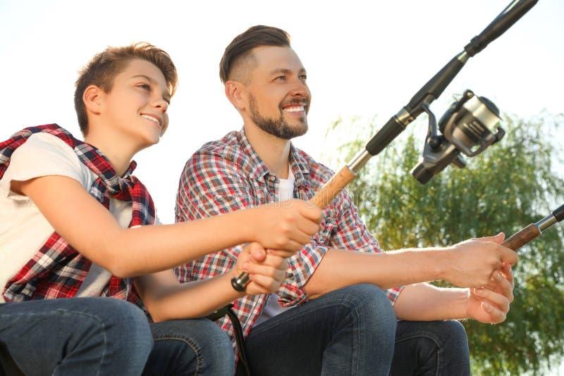 Vater und Sohn, die zusammen vom Flussufer fischen stockbild