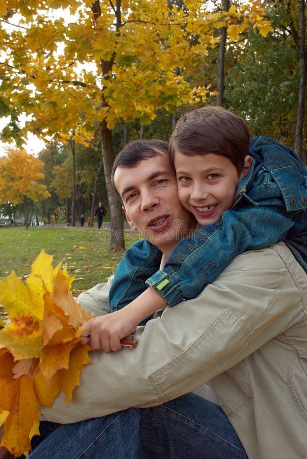 Vater und Sohn in einem Herbstpark lizenzfreie stockfotos
