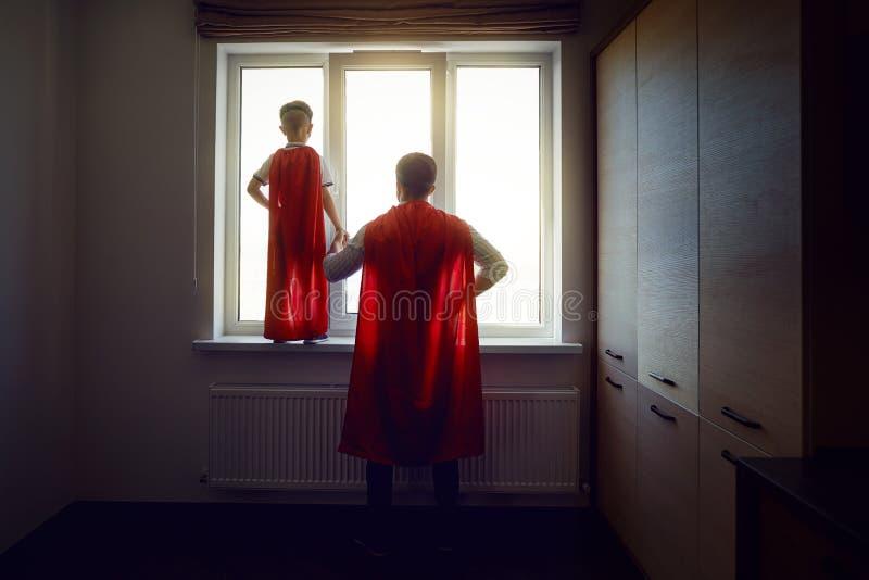 Vater und Sohn am Fenster im Raum lizenzfreies stockfoto