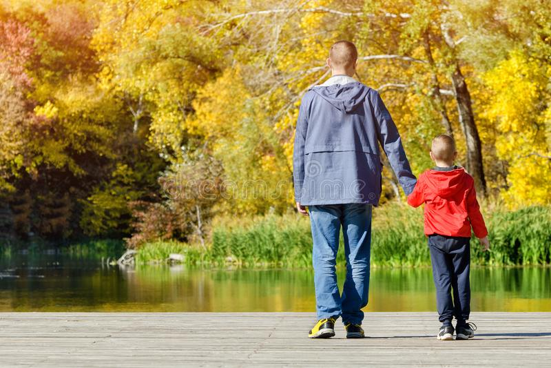 Vater und Sohn gehen entlang den Pier Herbst, sonnig hinteres v lizenzfreie stockfotos