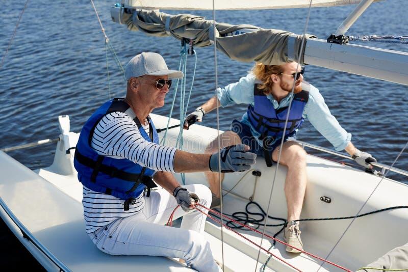 Vater und Sohn im Segelboot lizenzfreies stockfoto