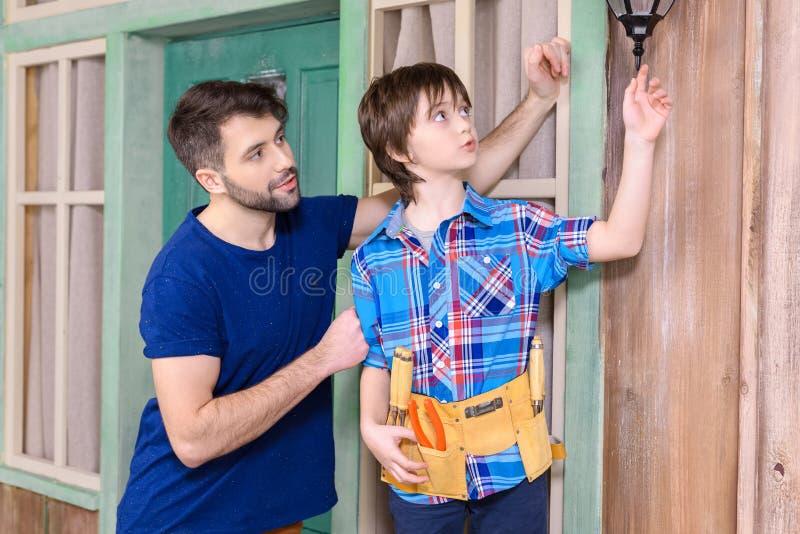 Vater und Sohn im Werkzeug schnallen Stellung zusammen um und schauend weg auf Portal stockfotos