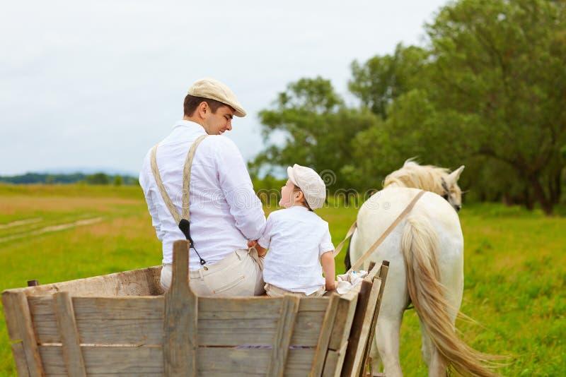 Vater und Sohn, Landwirte reiten einen Pferdewarenkorb lizenzfreies stockfoto