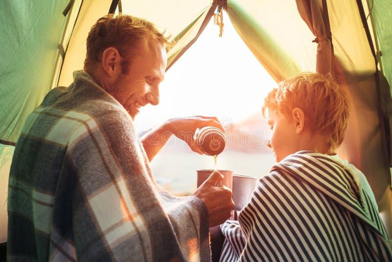 Vater und Sohn mit dem großen Becher Tee zusammen sitzend im Zelt nennwert lizenzfreie stockfotos