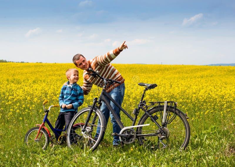 Vater und Sohn mit Fahrrädern auf Landfeld mit Blumen in sonnigem stockbild