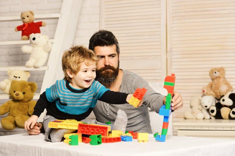 Vater und Sohn mit fröhlichen Gesichtern stellen bunten Roboter her lizenzfreies stockfoto