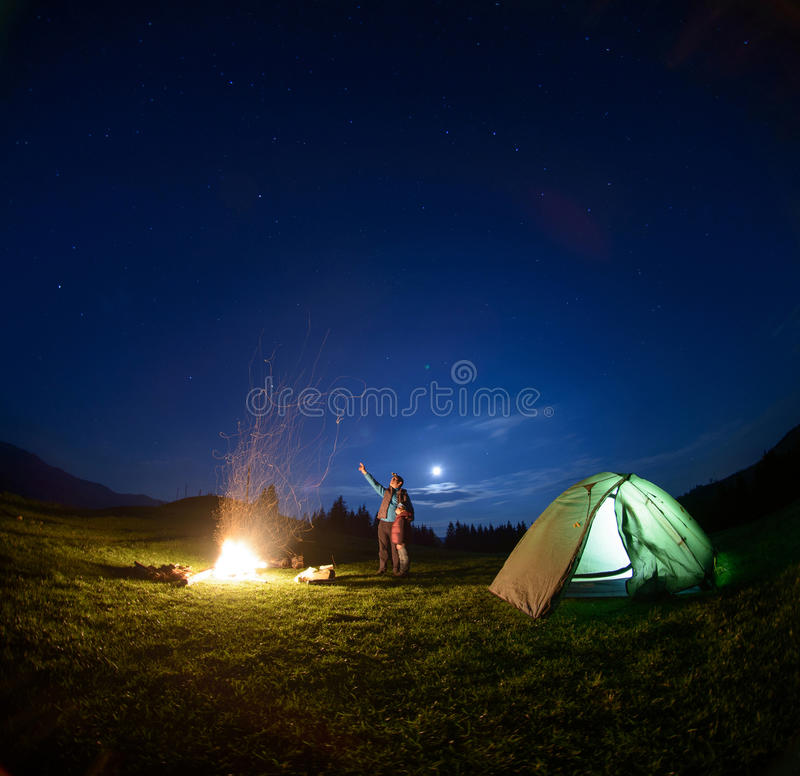 Vater und Sohn nahe Lagerfeuer und Zelt unter nächtlichem Himmel stockfotos