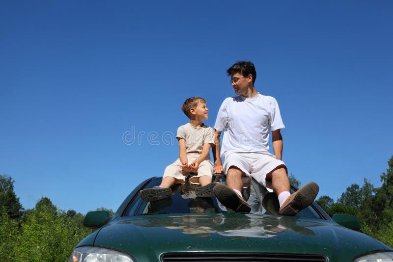 Vater und Sohn sitzen auf Dach des Autos am Tag lizenzfreies stockfoto