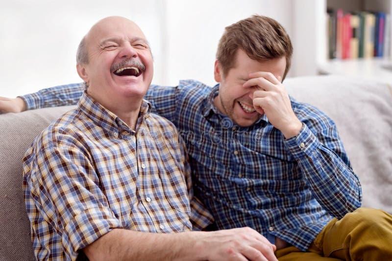 Vater und Sohn sitzen auf dem Sofa im Wohnzimmer und erinnern sich an Witz stockfotos